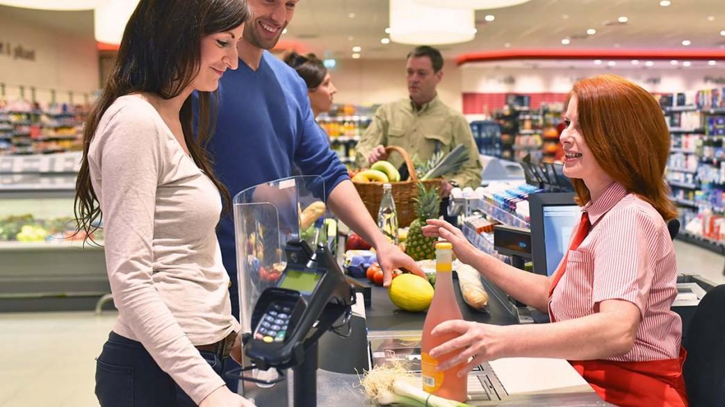 Menschen an der Kasse im Sueprmarkt - Einkauf von Lebensmitteln